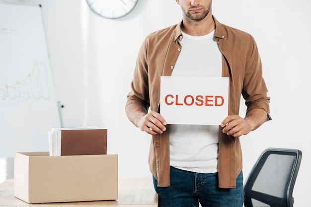 Homem de close-up segurando cartaz de fechado