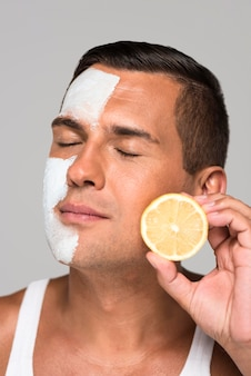Homem de close-up segurando metade do limão