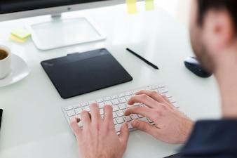 Homem de colheita digitando no teclado do computador