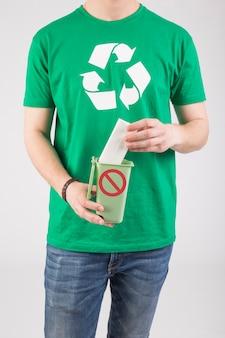 Homem de colheita em t-shirt verde com sinal ecológico