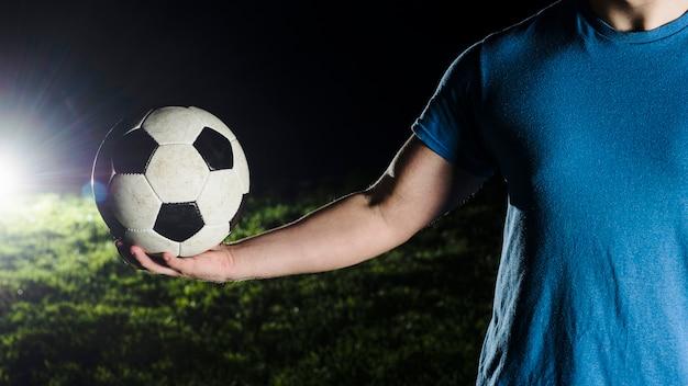 Homem de colheita segurando uma bola de futebol