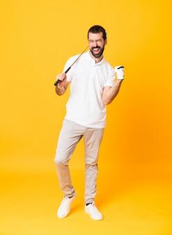 Homem de comprimento total sobre parede amarela isolada jogando golfe e comemorando uma vitória