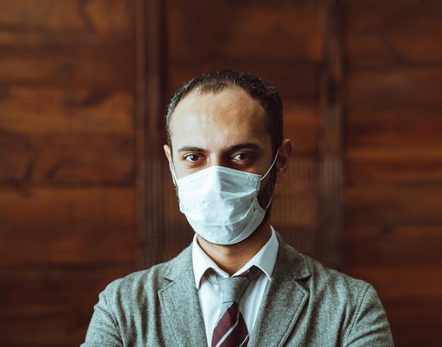 Homem de confiança na máscara protetora ficar sozinho no escritório