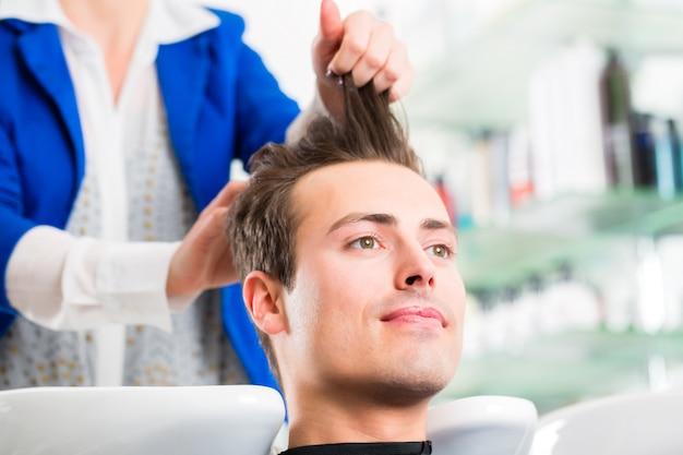 Homem de conselhos de cabeleireiro no corte de cabelo na barbearia