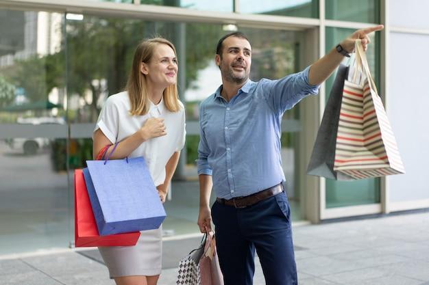 Homem de conteúdo compras com a esposa e mostrando-lhe algo ao ar livre