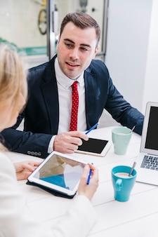 Homem de conteúdo conversando com os colegas na mesa