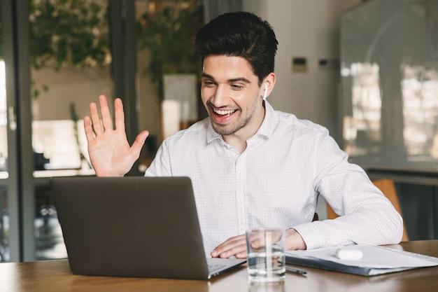 Homem de conteúdo do escritório vestindo camisa branca e fone de ouvido bluetooth, sorrindo enquanto acenava com a mão no laptop, durante uma videochamada ou bate-papo no escritório