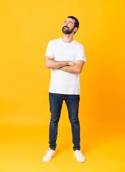 Homem de corpo inteiro com barba sobre parede amarela isolada, olhando para cima enquanto sorrindo