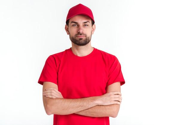 Homem de correio em pé, com os braços cruzados