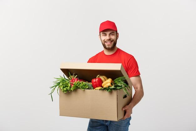 Homem de correio entrega caucasiano bonito supermercado uniforme vermelho com caixa de supermercado com frutas e vegetais frescos