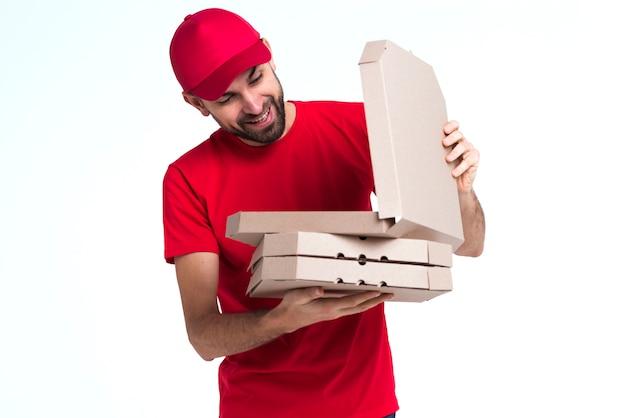 Homem de correio escolhendo em caixas de pizza