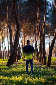 Homem de costas em uma floresta escura