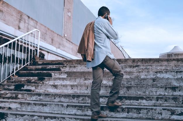 Homem de costas, falando por telefone celular nas escadas da cidade. cara casual bonito com smar