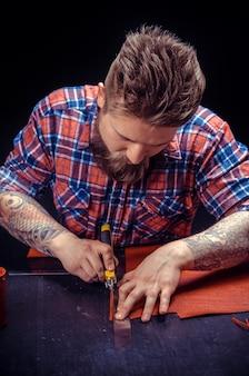 Homem de couro fazendo produtos de qualidade no estúdio.