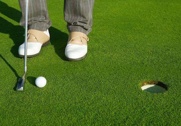 Homem de curso de buraco verde de golfe colocando bola curta