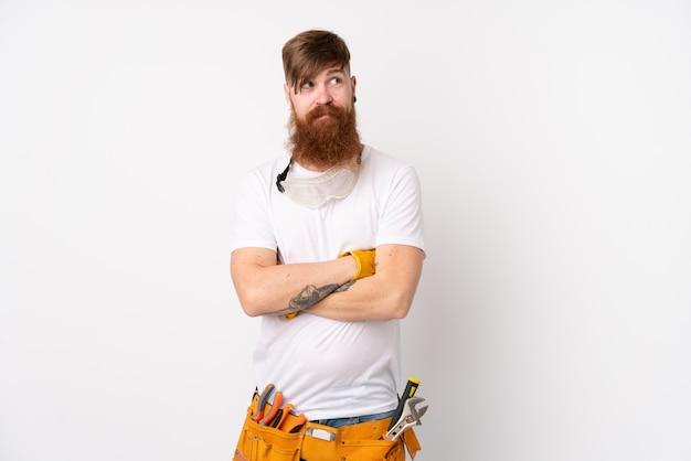 Homem de eletricista ruiva com barba longa ao longo da parede branca, pensando uma idéia