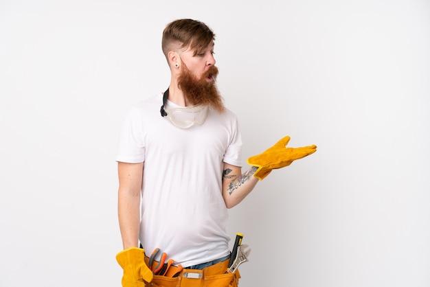 Homem de eletricista ruiva com barba longa isolado parede branca segurando copyspace imaginário na palma da mão