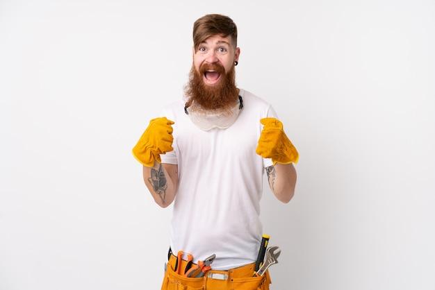 Homem de eletricista ruiva com barba longa sobre parede branca isolada, comemorando uma vitória