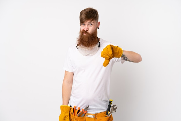 Homem de eletricista ruiva com barba longa sobre parede branca isolada, mostrando o polegar para baixo sinal