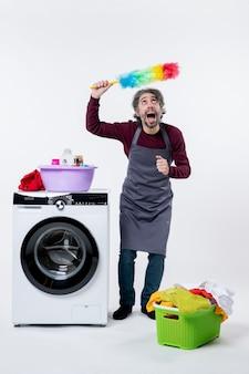 Homem de empregada com vista frontal segurando o espanador sobre a cabeça em pé perto do cesto de roupa suja da máquina de lavar no fundo branco