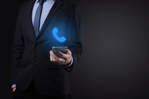 Homem de empresário de terno em fundo preto segurar o ícone de telefone. ligue agora conceito de tecnologia de serviço ao cliente do centro de suporte de comunicação empresarial.