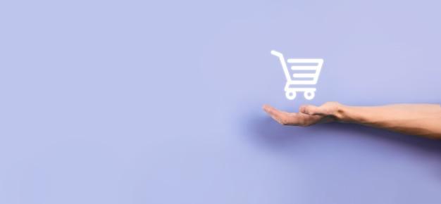 Homem de empresário segurando carrinho carrinho de compras mini carrinho na interface de pagamento digital de negócios. conceito de negócios, comércio e compras