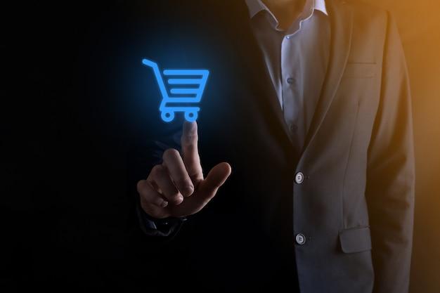 Homem de empresário segurando carrinho carrinho de compras mini carrinho na interface de pagamento digital de negócios. conceito de negócios, comércio e compras.