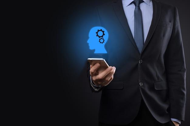 Homem de empresário segurando um ícone de homem com engrenagens na cabeça. inteligência artificial. avanços da tecnologia. robô. símbolo de contorno.