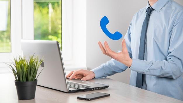 Homem de empresário segurar o ícone de telefone. ligue agora para o conceito de tecnologia de serviço ao cliente do centro de suporte de comunicação empresarial.