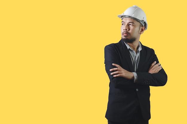 Homem de engenharia asiático usa capacete de segurança branco de crosse braço terno preto isolado no fundo amarelo. construção de controle capataz. trajeto de grampeamento.