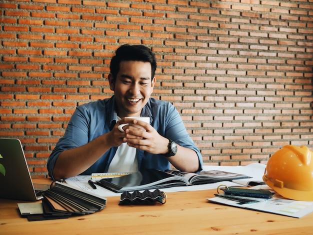 Homem de engenharia feliz tomando café no escritório de manhã