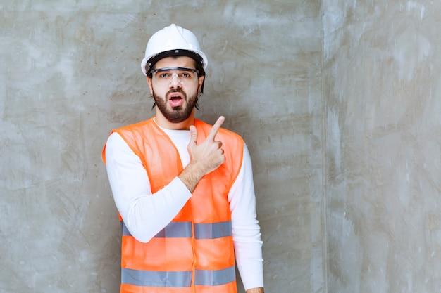 Homem de engenheiro com capacete branco e óculos de proteção, apontando para algo.