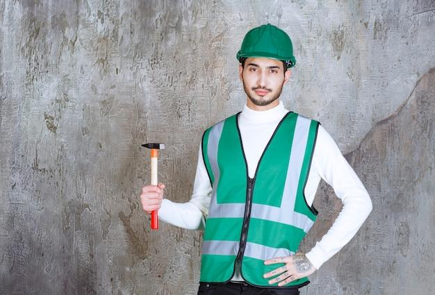 Homem de engenheiro de uniforme amarelo e capacete segurando um machado com cabo de madeira para reparo.