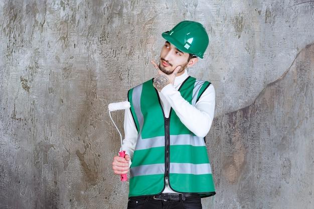 Homem de engenheiro de uniforme amarelo e capacete segurando um rolo aparador para pintura de parede e parece pensativo.