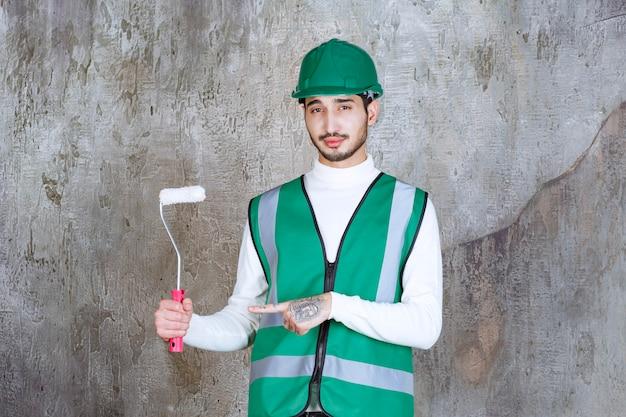 Homem de engenheiro de uniforme amarelo e capacete segurando um rolo de acabamento para pintura de parede.