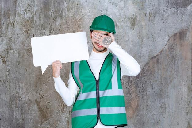 Homem de engenheiro de uniforme amarelo e capacete segurando uma placa de informações em branco e segurando a cabeça como cansado.