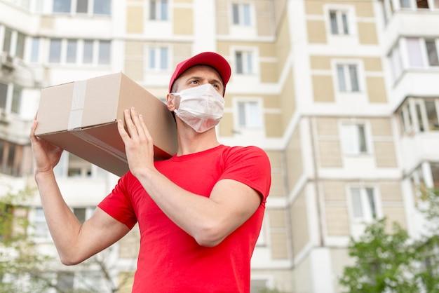 Homem de entrega de baixo ângulo segurando a caixa