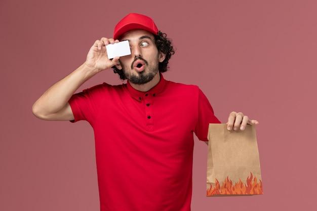 Homem de entrega de correio masculino de vista frontal, camisa vermelha e capa segurando pacote de comida e cartão na parede rosa.