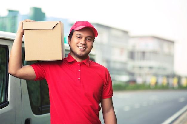 Homem de entrega de encomendas de um pacote através de um serviço de envio para casa. consignar a mão