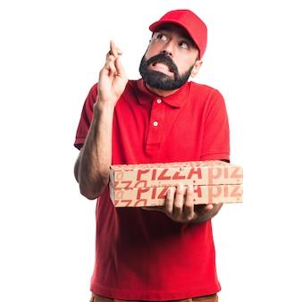 Homem de entrega de pizza com os dedos cruzados