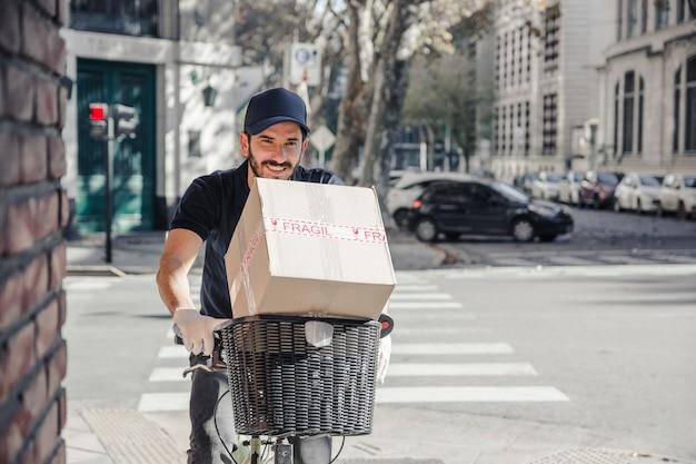 Homem de entrega feliz andando de bicicleta com caixa de papelão
