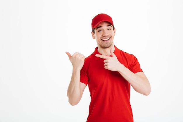 Homem de entrega jovem sorridente apontando isolado