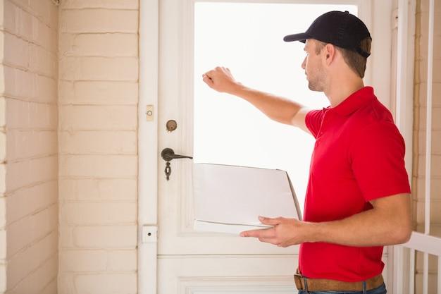 Homem de entrega segurando pizza enquanto bate na porta