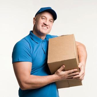 Homem de entrega sorridente segurando a caixa de papelão nos braços