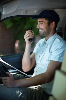 Homem de entrega sorridente usando walkie-talkie