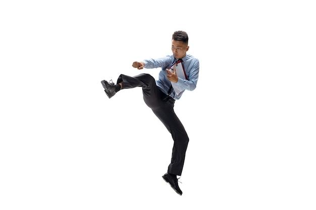 Homem de escritório praticando taekwondo na parede branca