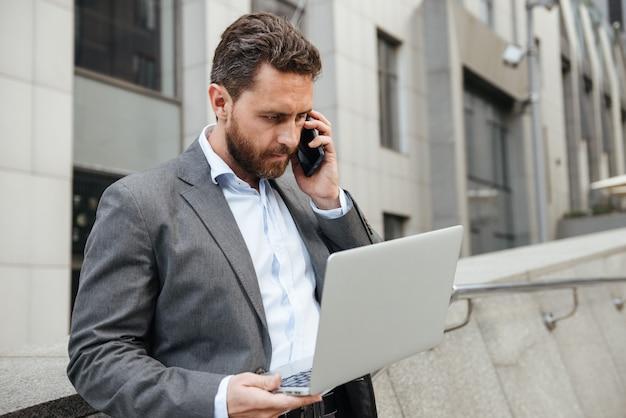 Homem de escritório sério em terno clássico, trabalhando em um laptop prateado e falando no celular, em pé perto do centro de negócios