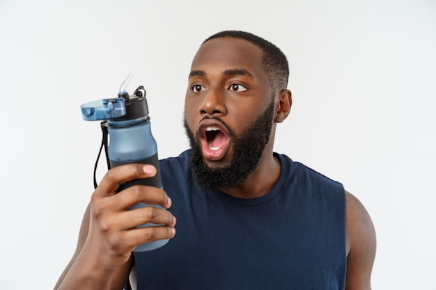 Homem de esporte americano africano atleta masculino com esportes em execução com telefone móvel e beber água de garrafa.
