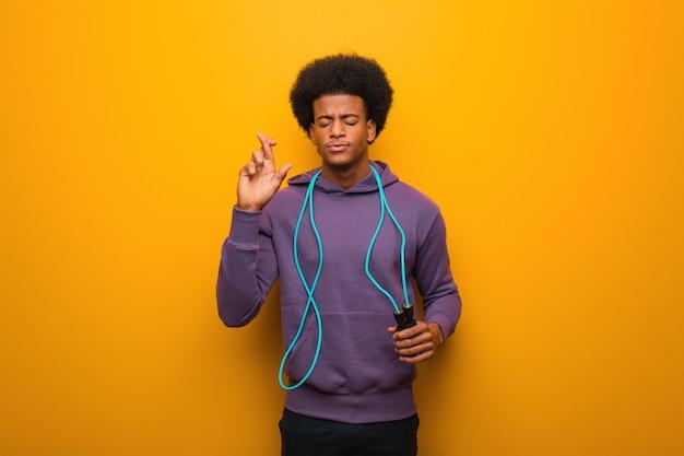 Homem de esporte americano africano jovem segurando uma corda de pular, cruzando os dedos por ter sorte
