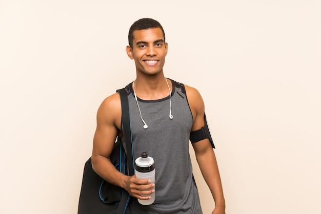Homem de esporte ao longo da parede com uma garrafa de água